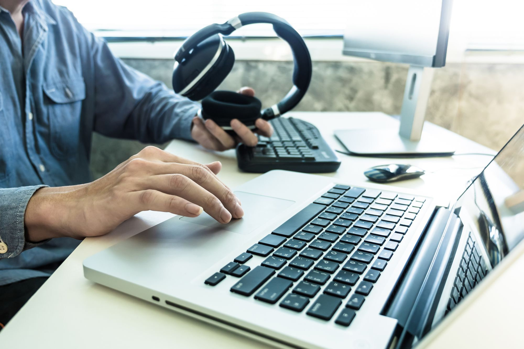 Male hands holding headphones and working on computer, Sound engineer concept