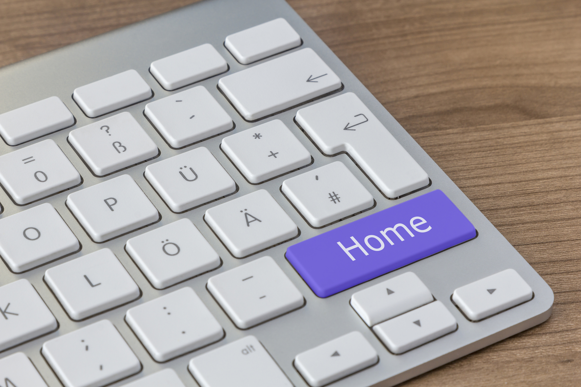 Home written on a large blue button of a modern keyboard on a wooden desktop